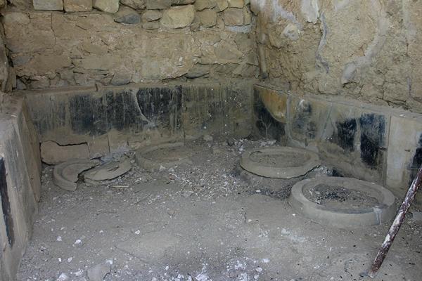 Lagerraum mit Fundamenten für die Vorratsgefäße (Pithoi) und sichtbaren Brandspuren.