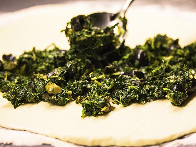 Gemüsemischung auf einer Hälfte des Teigrunds verteilen.