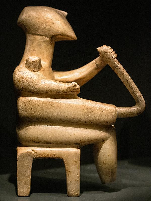 Ein Harfenspieler sitzt auf einem Hocker.