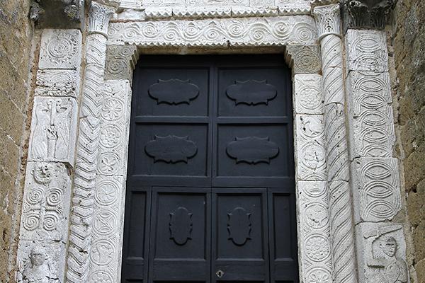 Das Portal ist aus Marmor. In der Mitte des Bogens befinden sich zwei Löwenköpfe.