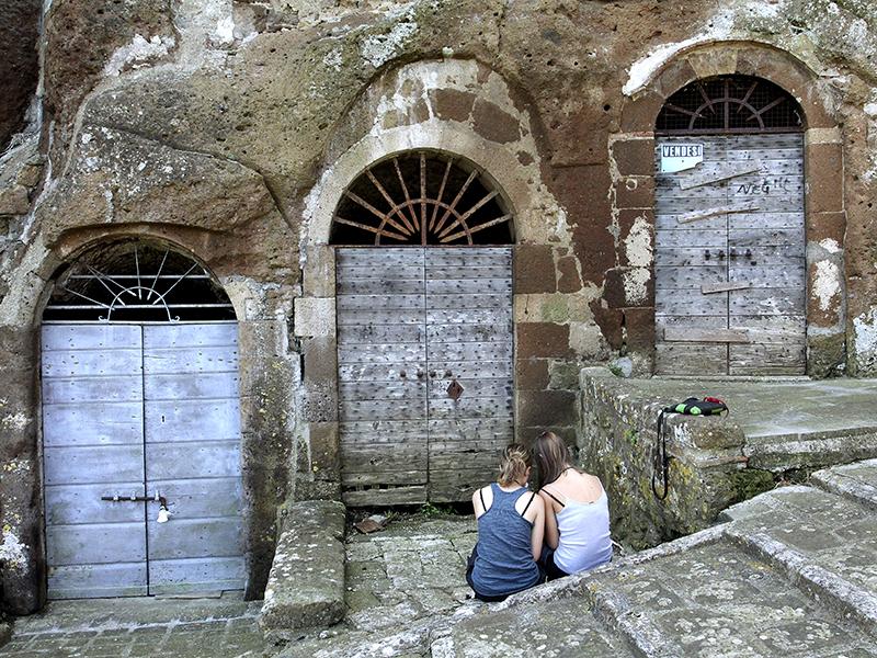 Zwei Mädchen sitzen vor den Eingängen der Weinkeller.