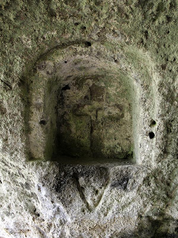 Das christliche Kreuz in der Wand einer Höhle.