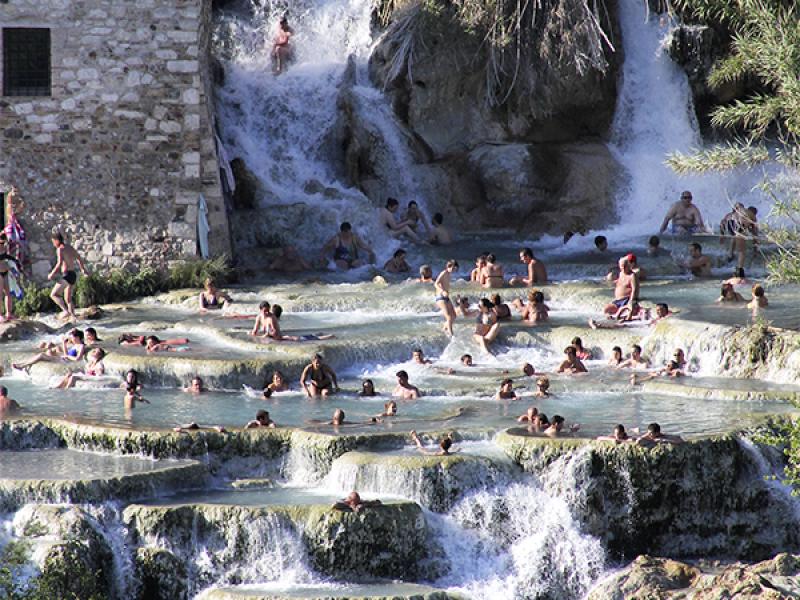 Das Wasser stürzt eine Felswand herunter, sammelt sich in einem Naturbecken und fällt dann wieder in stufenförmige Sinterbecken