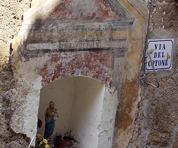 Heiligenfigur ein einer Mauernische.