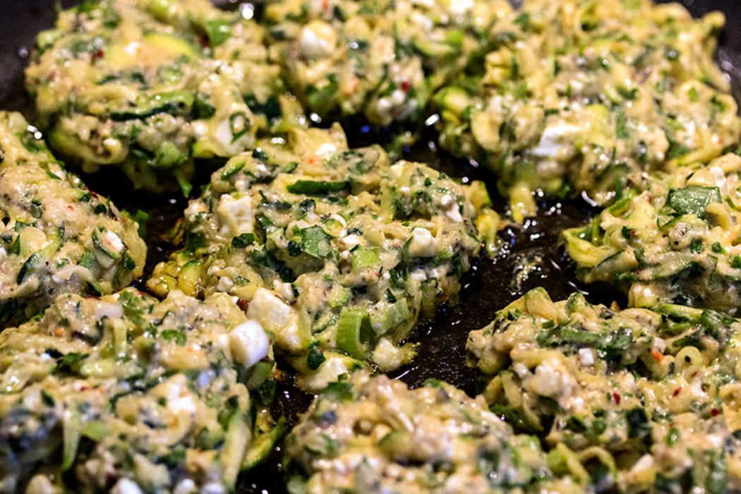 Zucchini-Puffer in Olivenöl braten.