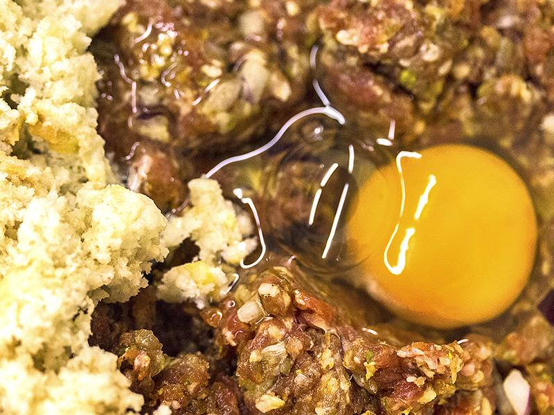 In den Fleischteig kommen die Gewürze, das eingeweichte Brot und Eier.