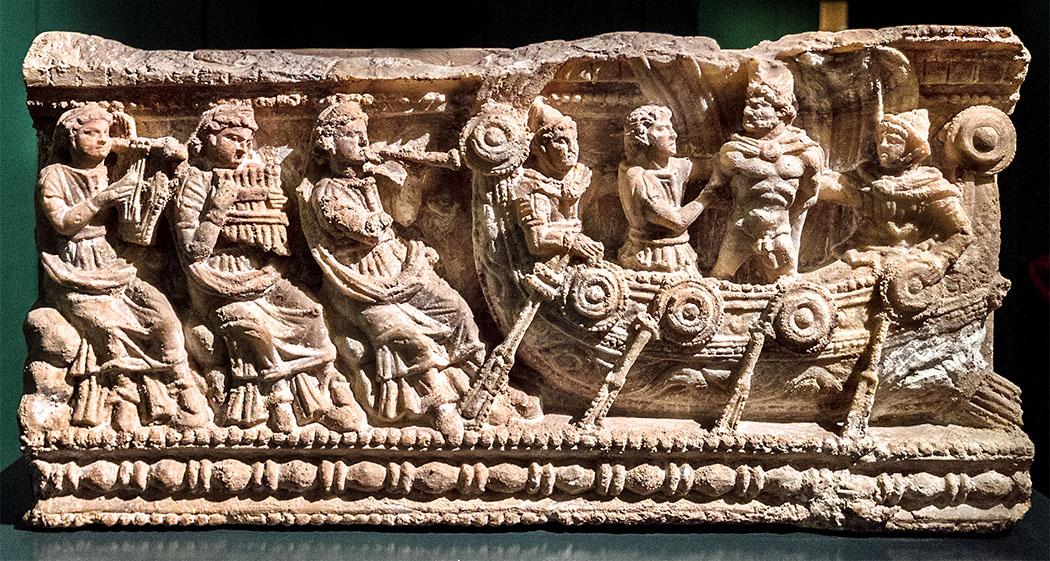 Volterra, Urne, auch volterraner urne genannt, 2. Jhd. v. chr Etruskische Alabaster-Urne aus dem 3./2. Jdh. v. Chr. Das Motiv zeigt wie Odysseus von Permedes und Eurylochus eilig am Schiffsmast festgebunden wird. Denn Odysseus wird vom zauberhaften Gesang der Sirenen angelockt. Jeder der diesem folgte war verloren und musste sterben. Foto: Museo Etrusco Guarnacci, Volterra