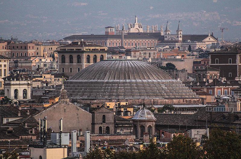 Die mächtige Kuppel des Pantheons, dahinter ragen die riesigen Heiligenfiguren des Laterans aus dem Dächermeer.