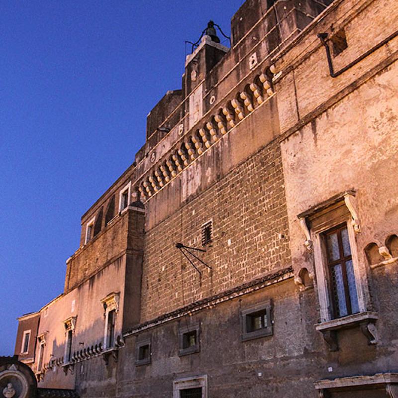 Die Nacht senkt sich über Rom. Die alten Mauern schimmern in warmen Farben.
