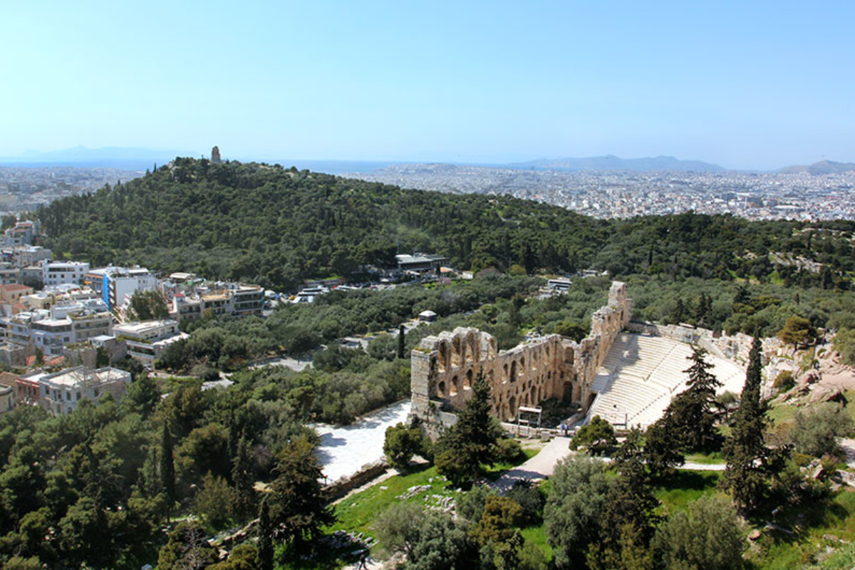 Als wir unseren Blick vom Parthenon abwenden, versinken wir lange im herrlichen Anblick des Saronischen Golfs und seiner großen Inseln Ägina (links) und Salamis. Unter uns liegt das Odeion aus römischer Zeit, gegenüber auf dem gewaldeten Hügel das Grabmal des Philopappos.