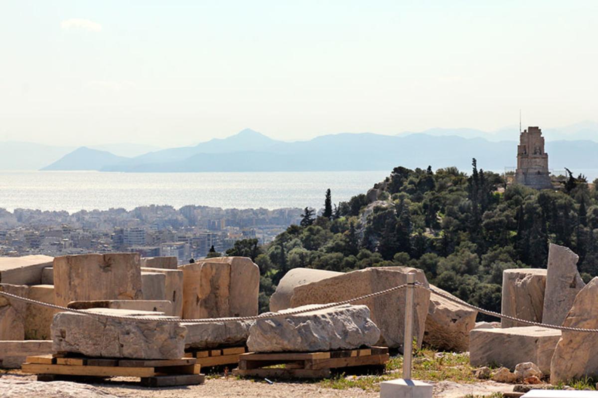 Das Häusermeer von Athen, dahinter der Saronische Golf mit der Insel Ägina. Rechts im Bild das Philopappos-Monument.