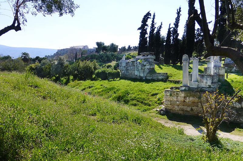 Der antike Kerameikos-Friedhof lag außerhalb der Stadtmauern. Die Akademiestraße beginnt am Dipylon-Tor und führt zur Akademeia, dem Sitz der von Platon begründeten Philosophenschule. Im Hintergrund ist das Parthenon sichtbar.