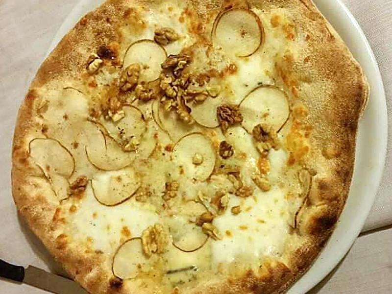 Pizza mit Birnenscheiben, Käse und Walnüssen.
