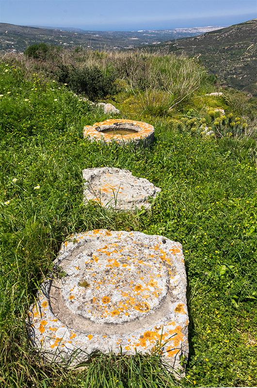 Einsame Mühlsteine aus lange vergangenen Zeiten blicken hinunter zum Meer und nach Sitia.