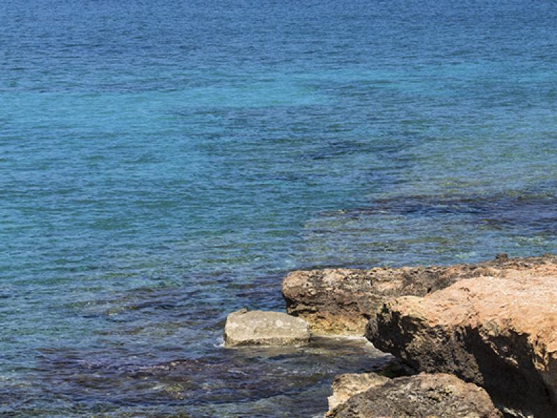 Türkisblaues schimmert das Wasser, im Hintergrund die ersten kleinen Ferienanlagen von Xerokampos.