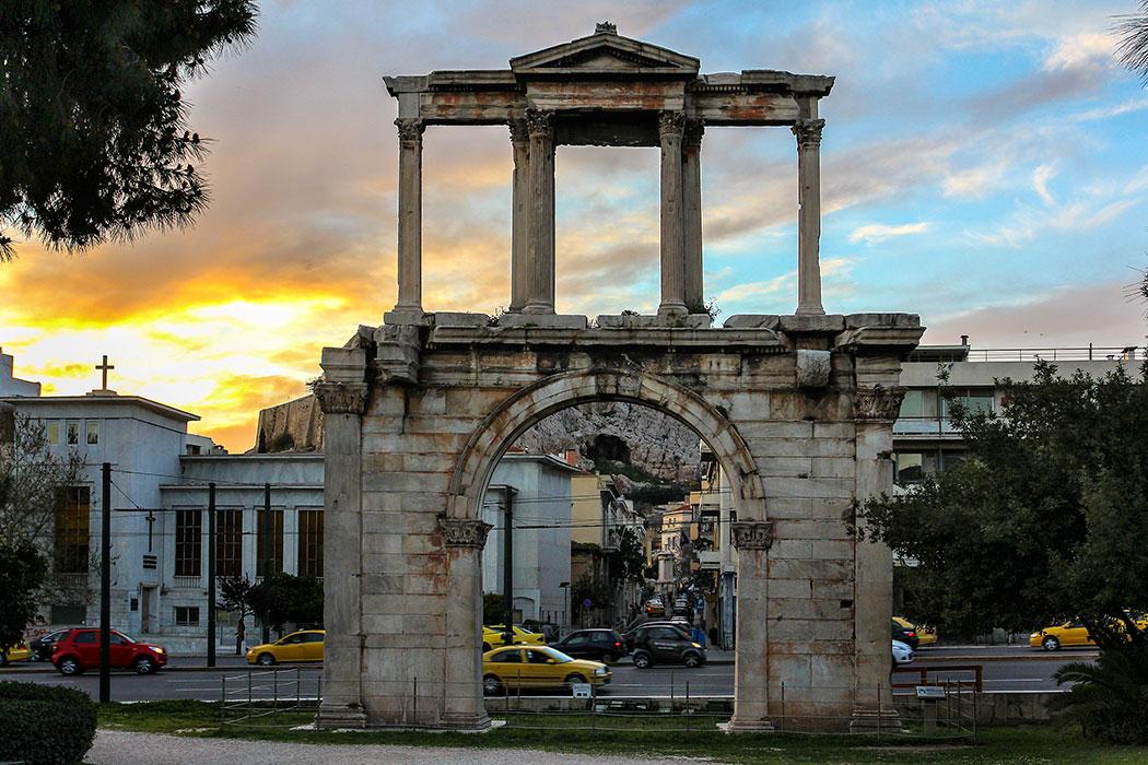 Der Autoverkehr braust hinter dem ehrwürdigen Hadrianstor vorbei. Dahinter ist der Felsen der Akropolis sichtbar.