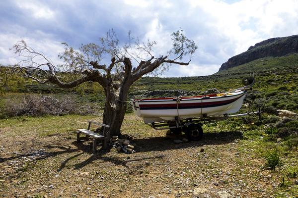 Einsame Bank, einsamer Baum und ein einsames Boot am Amatos-Strand.