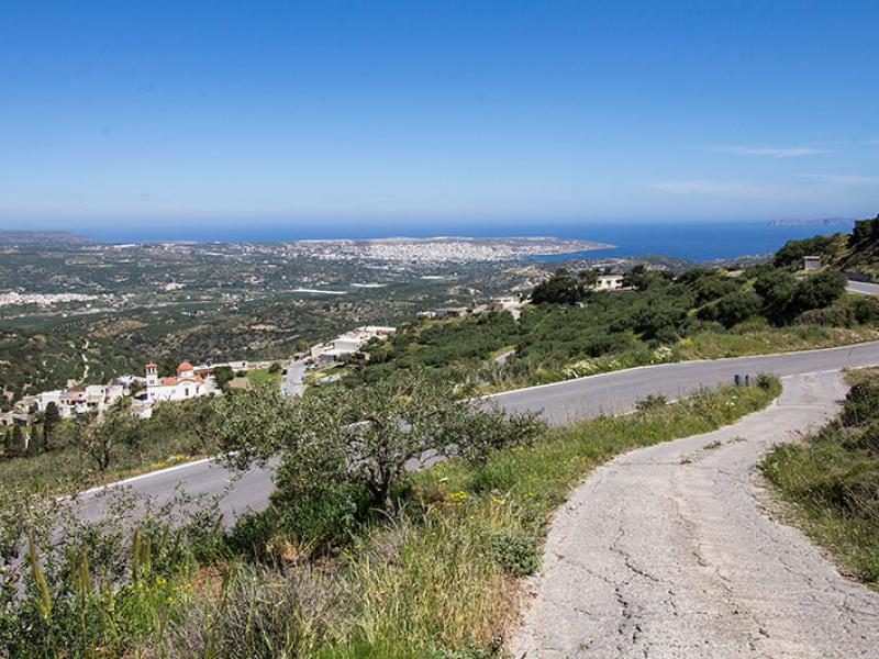 Panorama-Aussicht von der Dorfstraße in Kato Drys hinunter nach Stavromenos, die Stadt Sitia und das Meer. Ganz rechts die Inselgruppe der Dionysaden.