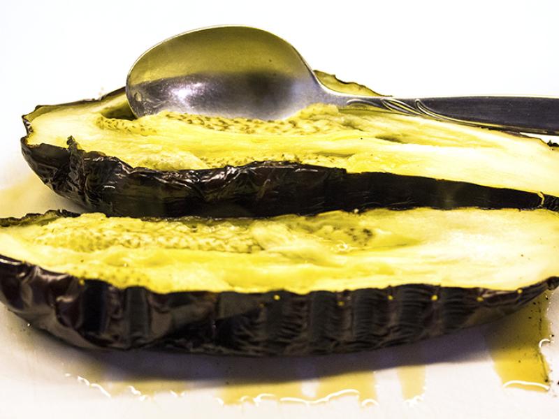 Die Auberginen längs halbieren und das Fruchtfleisch mit einem Löffel aus der Schale lösen.