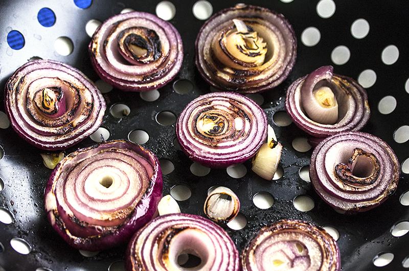 Die Zwiebeln in dicke Scheiben schneiden und in der Gemüsepfanne grillen.