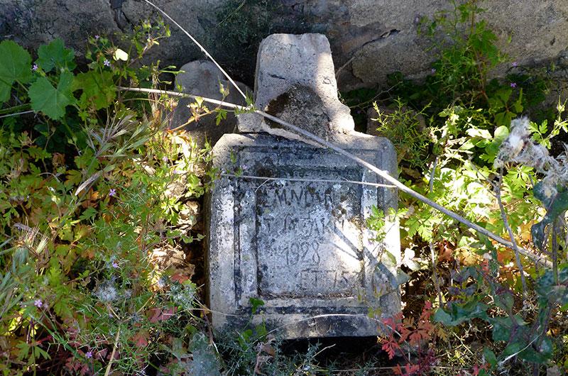 Ein alter Grabstein lehnt an der Friedhofsmauer.