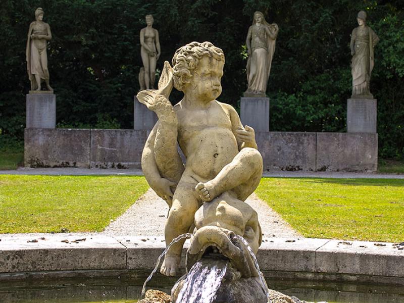 Hinter dem Delphinbrunnen sind weitere Skulpturen aufgestellt. Sie zeigen Paris mit dem Apfel als Gegenstand des Streits, Aphrodite, Hera und Pallas Athene (von links nach rechts).