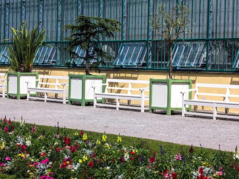 Im Sommer laden bequeme Holzbänke und mediterrane Bäume vor dem Eisernen Haus zum Pausieren ein.