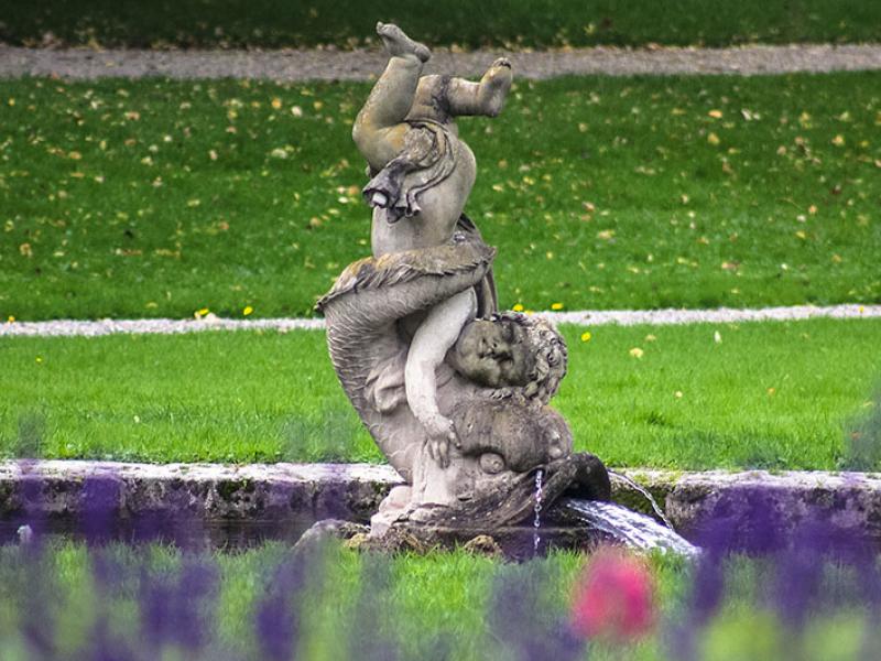 Der Brunnen mit der Knabenskulptur und dem Delphin steht gegenüber des Gewächshauses.