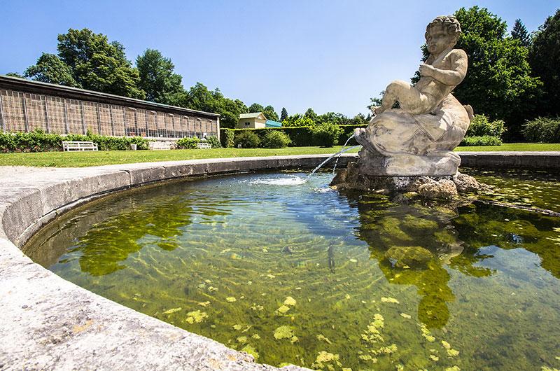 Ein weiterer Brunnen befindet sich vor dem Geranienhaus, mit einer Knabenskulptur die auf einem Delphin reitet.