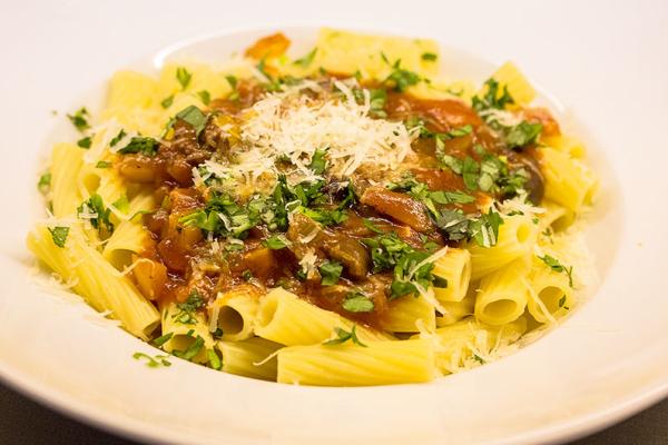 Pasta mit der Tomatensauce, den Kräutern und frisch geriebenen Pecorino bestreuen.