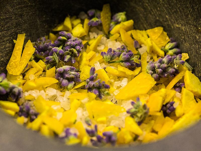 Orangenschale und Blüten mit dem Messer zerkleinern, erst dann mit dem Meersalz in den Mörser geben.