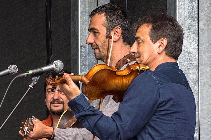 Die Musiker begleiten mit Geige, Gitarre und Bongo.