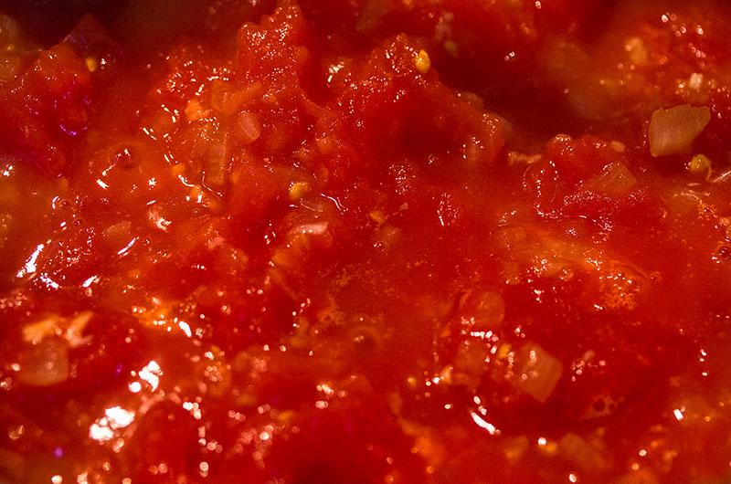 Tomaten mit Zwiebeln und Knoblauch mindestens 45 Minuten bei kleiner Hitze köcheln lassen.
