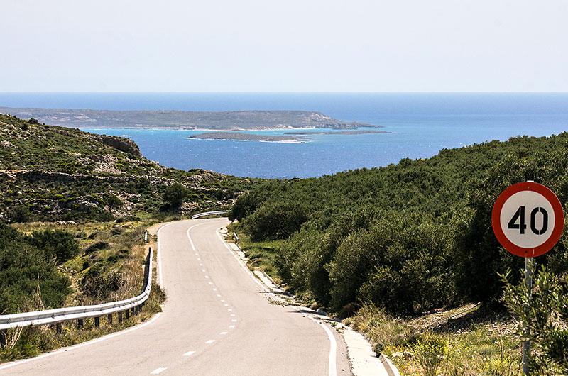 Die Straße führt von Agia Triada zum Meer hinunter, vor uns liegt unbewohnte die Insel Koufonisi.