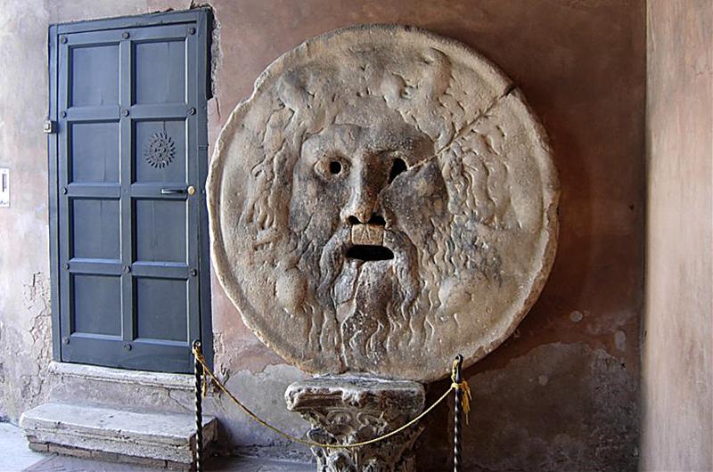 """Die runde antike Steinmaske mit geöffneten Mund, die als """"Mund der Wahrheit"""" (Bocca della Verità) bezeichnet wird, stammt vermutlich von einem Brunnen und stellt den Meeresgott Triton dar."""