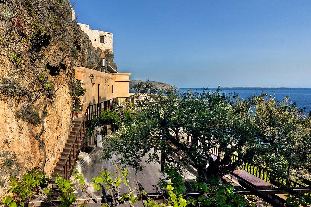 reise-zikaden.de - Griechenland, Kreta, Lasithi, Sitia, Goudouras, Moni Kapsa, Kloster, Innenhof. - Moni Kapsa liegt in steiler Lage über dem Meer. Im schattigen Innenhof befindet sich eine Felsenquelle die das ganze Jahr Wasser spendet. Im Hintergrund ist die Insel Koufonisi sichtbar.