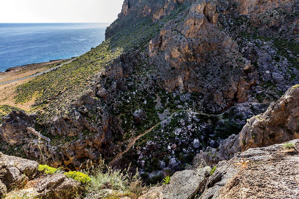 """reise-zikaden.de - Griechenland, Kreta, Ostkreta, Moni Kapsa, Makry Gialos, Goudouras, Perivolakia, Schlucht - Blick in die Perivolakia-Schlucht beim Kloster Moni Kapsa. Wir befinden uns an der einstigen Wohnhöhle des Eremiten """"Gerontogiannis"""". Schmale Pfade von Wanderern, Ziegen und Schafen sind an der Westflanke der Schlucht sichtbar."""