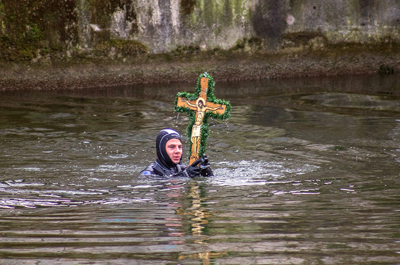 Der Schwimmer bringt das Holzkreuz zügig ans Ufer.
