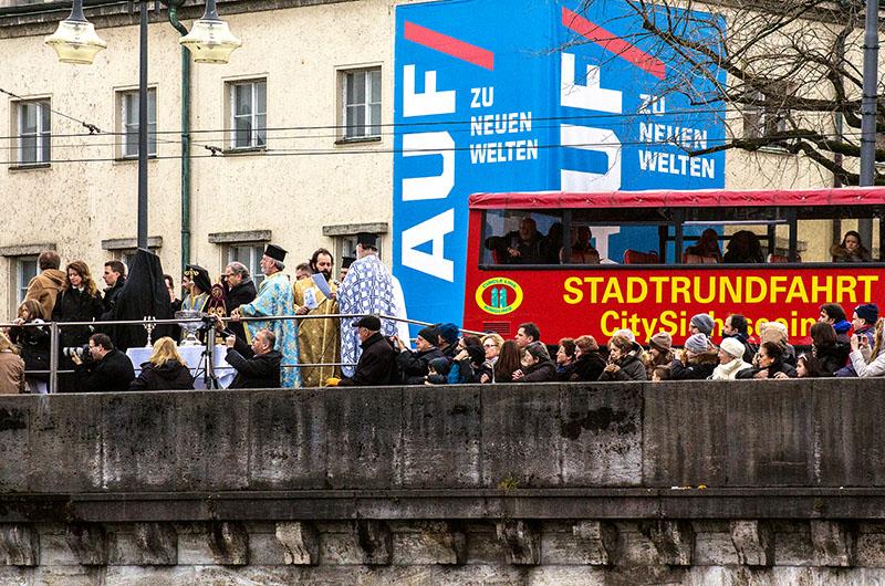 Die Priester erwarten das Holzkreuz, die Touristen im Bus bestaunen die Zeremonie.