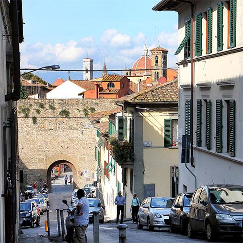 Das Stadttor Porta San Miniato im Viertel San Niccolò in Oltrarno. Dahinter ist der Glockenturm und die Domkuppel zu sehen.