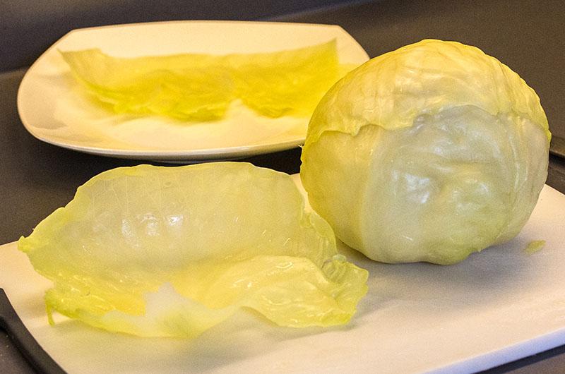 Weißkohlrouladen mit Zitronen-Ei-Sauce. Die großen Kohlblätter halbieren, die Mittelrippen wegschneiden.