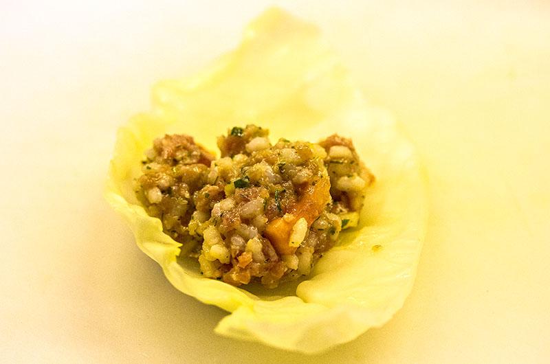 Weißkohlrouladen mit Zitronen-Ei-Sauce. Jeweils einen Esslöffel der Füllung auf ein Kohlblatt legen, zuerst die Seiten einschlagen und dann fest aufrollen.