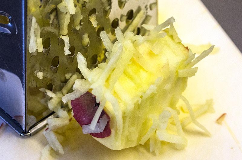 Die Äpfel schälen und im Ganzen mit der groben Raspel der Küchenreibe zerkleinern.