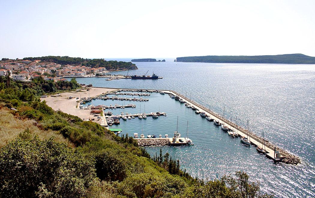 Pylos in der Navarinobucht Die gemütliche Hafenstadt Pylos mit ihrem Fischerhafen, kleine Frachtschiffe legen am großen Kai an. Im Hintergrund das Südende der Insel Sphakteria, links daneben die kleine Insel Tsichli-Baba.