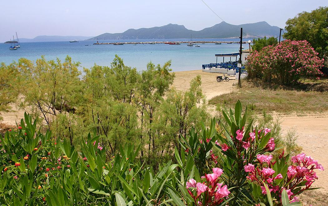Hier schlagen die Herzen des Griechenland-Fans höher: Blaues Meer und Sandstrand, im Hintergrund kleine Inseln, dazu eine Strandtaverne mit blühendem Orleander.