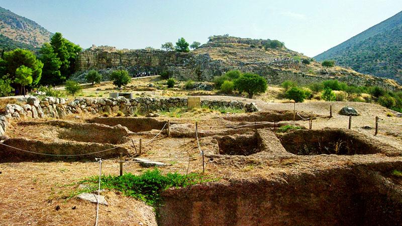 Palast und Burg von Mykenee, im Vordergrund freigelegte Gräber. Die Anlage erhebt sich auf einem steilen Hügel im Norden der Ebene von Argos. Der Mythos vom Kampf zwischen den Brüdern Atreus und Thyestes in Mykene, ist durch die archäologische Ausgrabungen bestätigt worden. Foto: Wikipedia, Bgabel