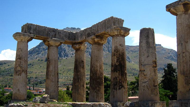 Der dorische Apollontempel im Ausgrabungsareal der antiken Stadt Korinth, dahinter auf einem steilen Felsen liegt die Festung Akrokorinth. Foto: flickr, Quillons