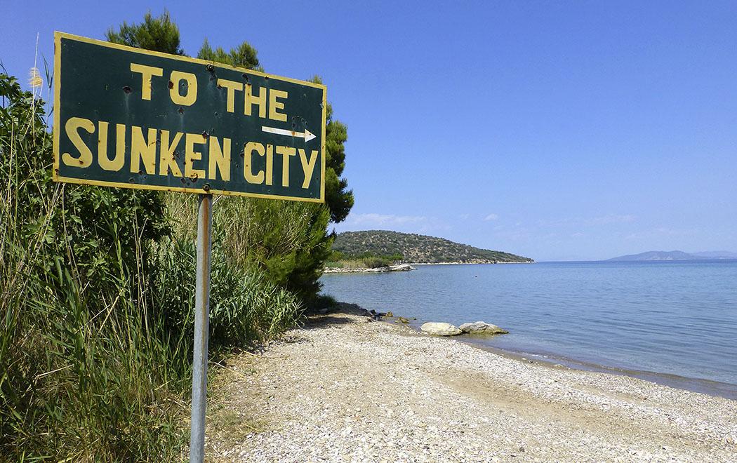 Ein großes Schild am Strand weist den Weg zu den Unterwasserruinen.