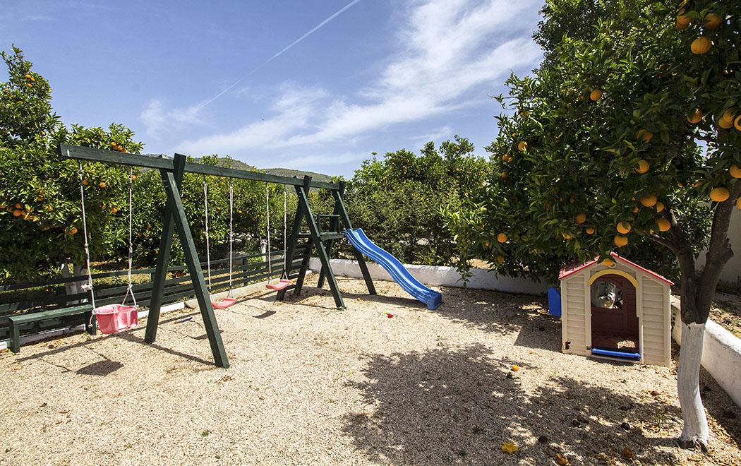 Der Kinderspielplatz bietet Schaukeln, eine Rutsche und einn kleines Häusen an.