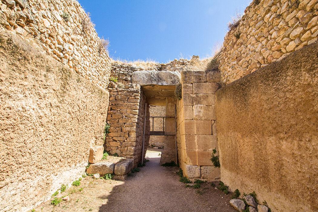 Etwa 70 Jahre nach seiner Errichtung erhielt das Aigisthos Grab eine neue Fassade aus Poros-Kalkstein mit Schmuckelementen. Die Fassade (links) bestand ursprünglich aus grob behauenen Steinen.